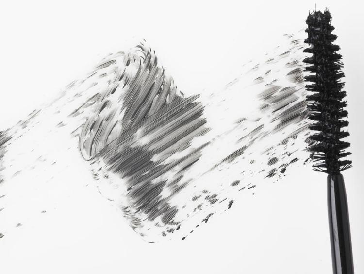 Mascara brush leaving traces of mascara on a white background